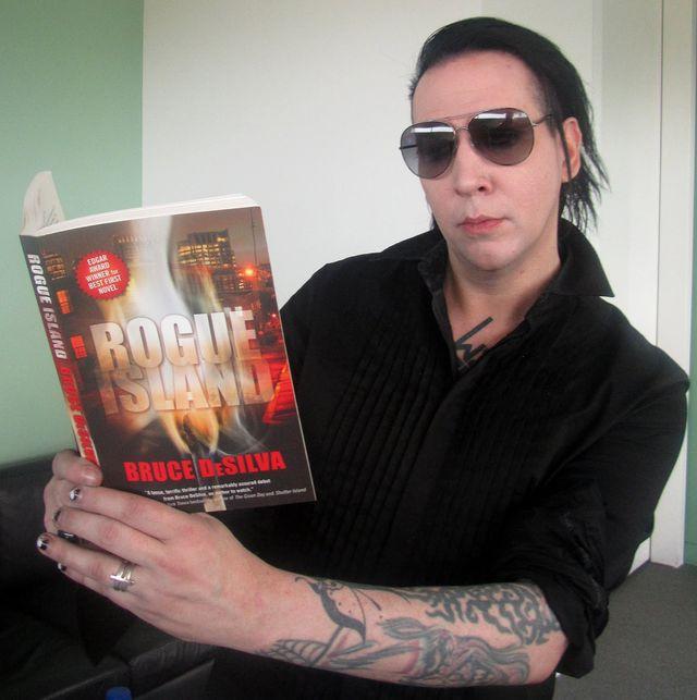 Marilyn Manson sans maquillage qui lit un livre